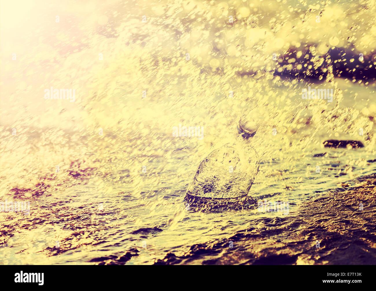 Bouteille vide avec de l'eau des vagues sur la plage, retro vintage filtré. Photo Stock