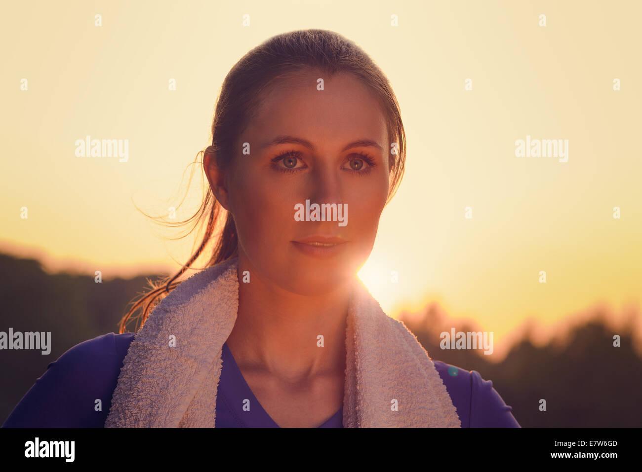 Jolie femme au coucher du soleil à l'extérieur par le rétro-éclairage orangé du soleil provoquant une poussée autour de son visage Banque D'Images