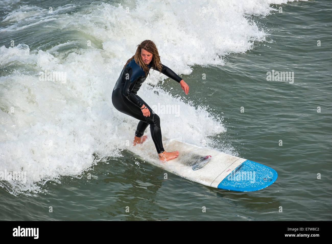 Surfer avec des dreadlocks en noir bottines équitation sur des vagues de surf comme il casse le long de la Photo Stock