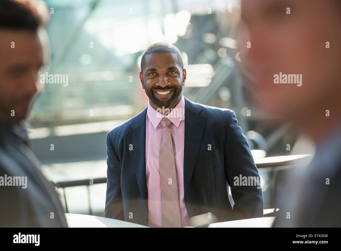 Un homme d'affaires assis souriant avec confiance, dans un groupe avec deux autres. Photo Stock