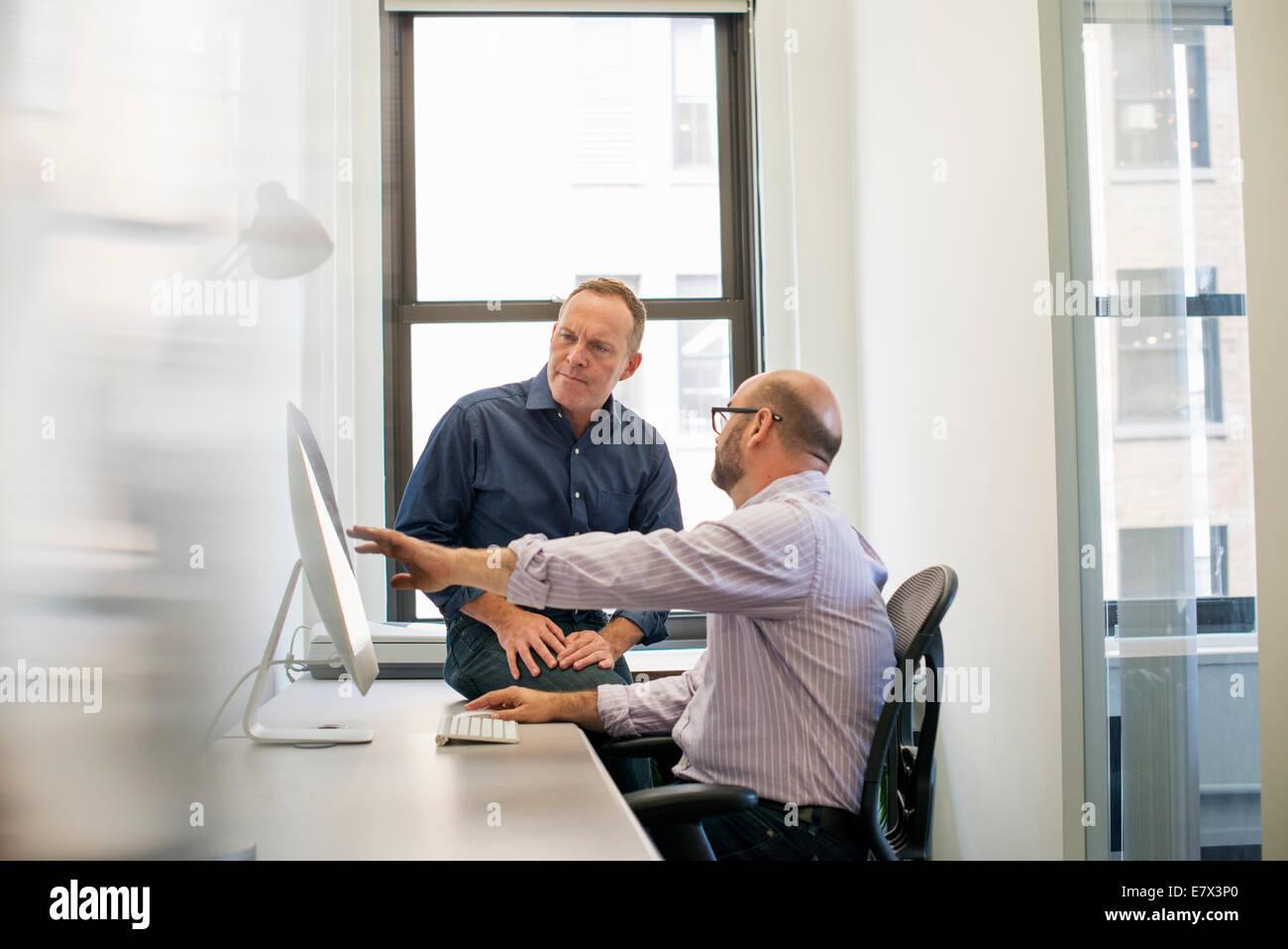 Deux collègues dans un bureau de parler et se référant à l'écran d'un ordinateur. Photo Stock