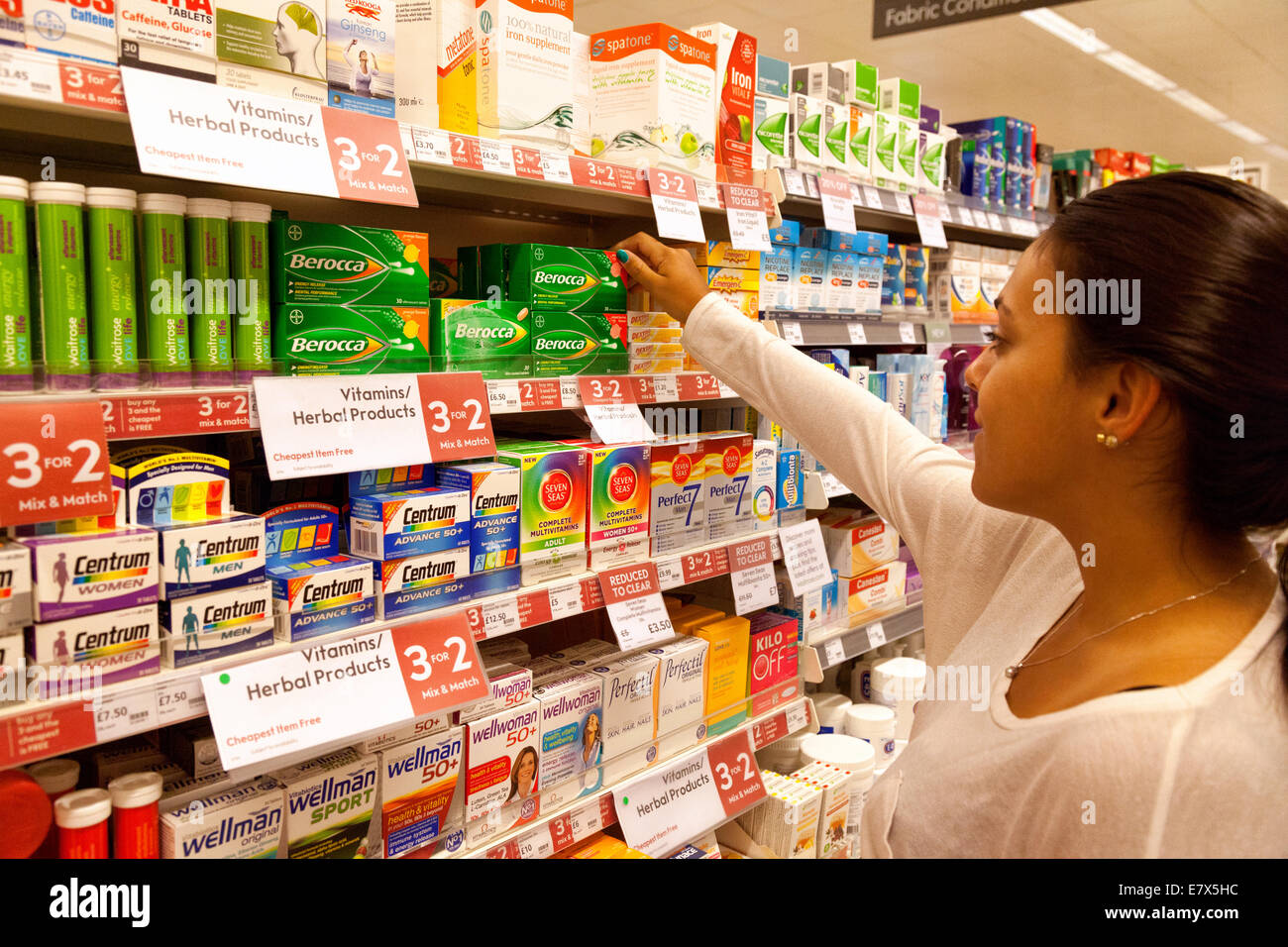Young woman shopping for / acheter vitamines supermarché Waitrose , Newmarket Suffolk, UK Photo Stock