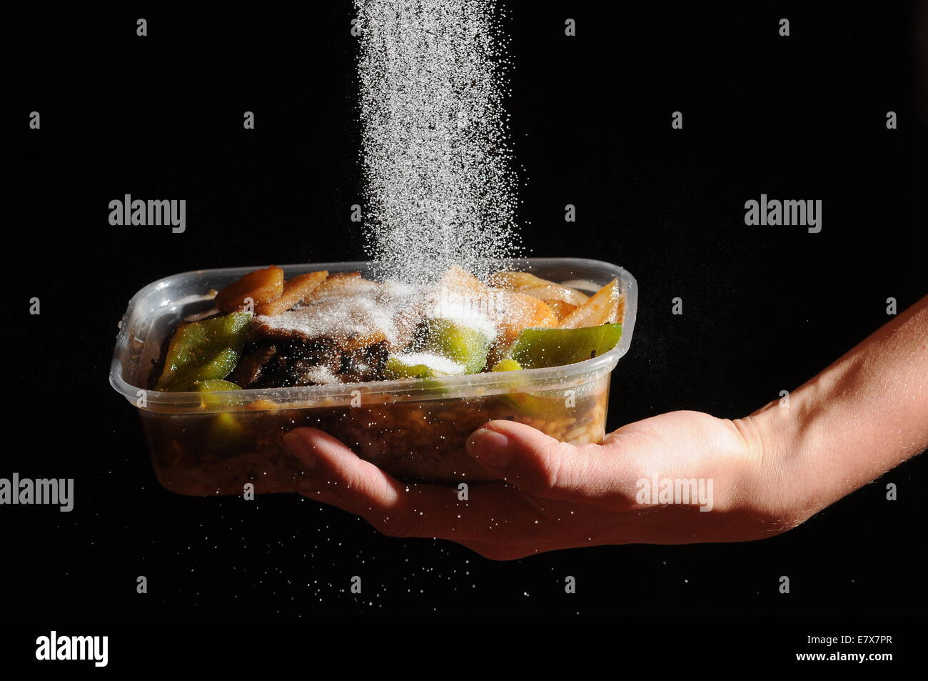 La nourriture à emporter avec du sel est versé d'en haut. Des niveaux élevés de sel dans Photo Stock