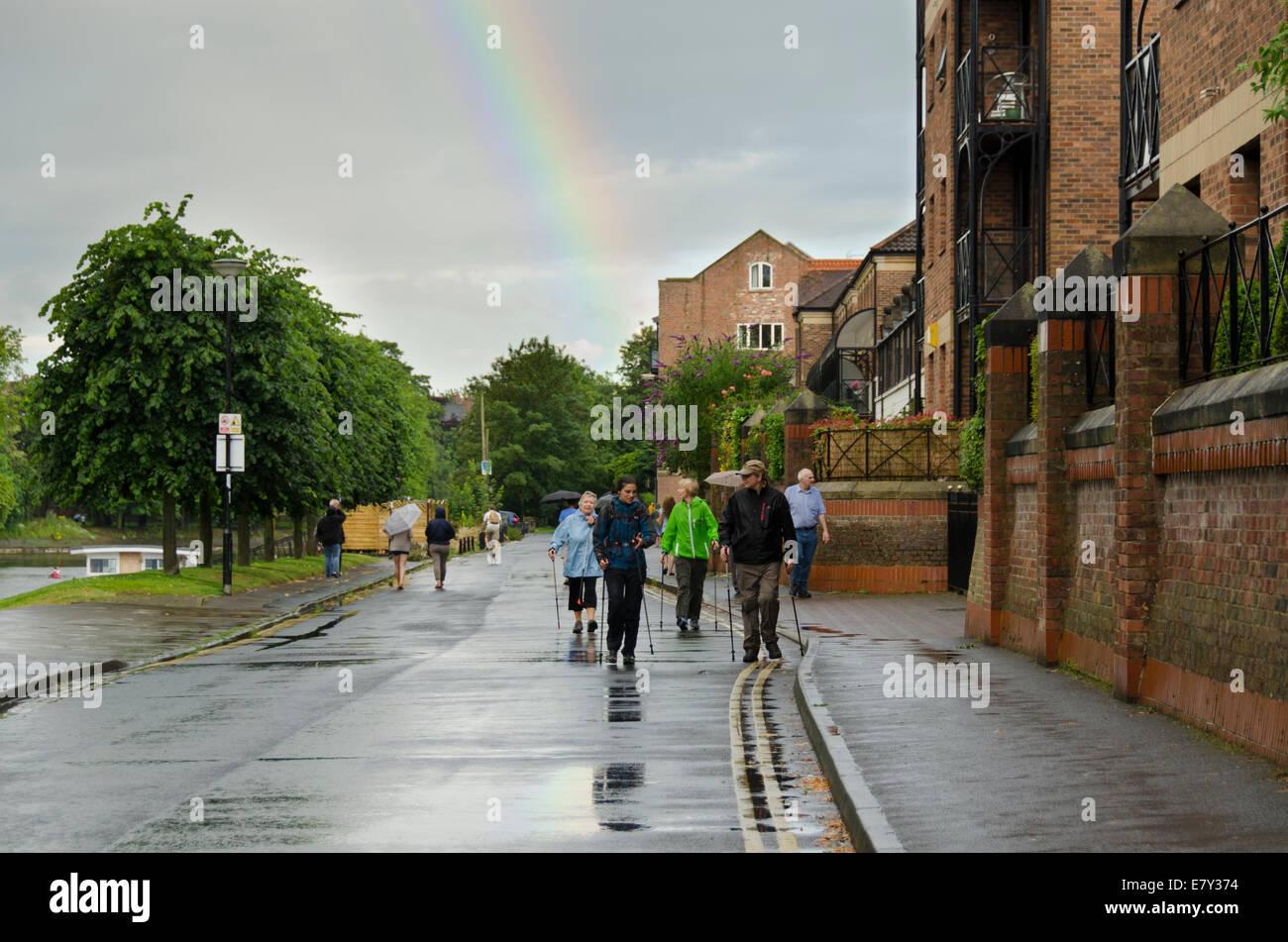 En haut arc-en-ciel nuageux gris après une averse soudaine de pluie & wet personnes marchant sur Riverside Road, York, North Yorkshire, Angleterre, Royaume-Uni, Banque D'Images