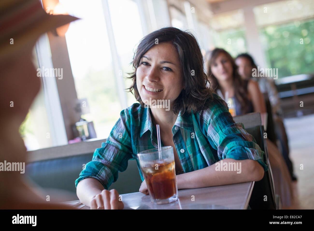Une femme assise à un diner en regardant son compagnon. Une boisson fraîche avec une paille. Photo Stock