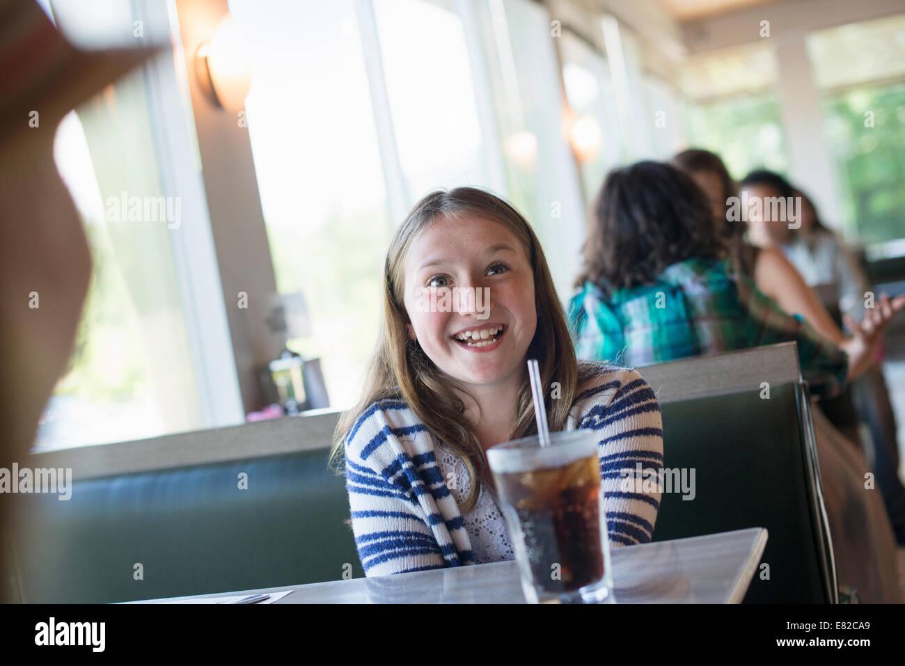 Un enfant assis à un repas avec un grand verre de boisson gazeuse dans un verre avec une paille. Photo Stock