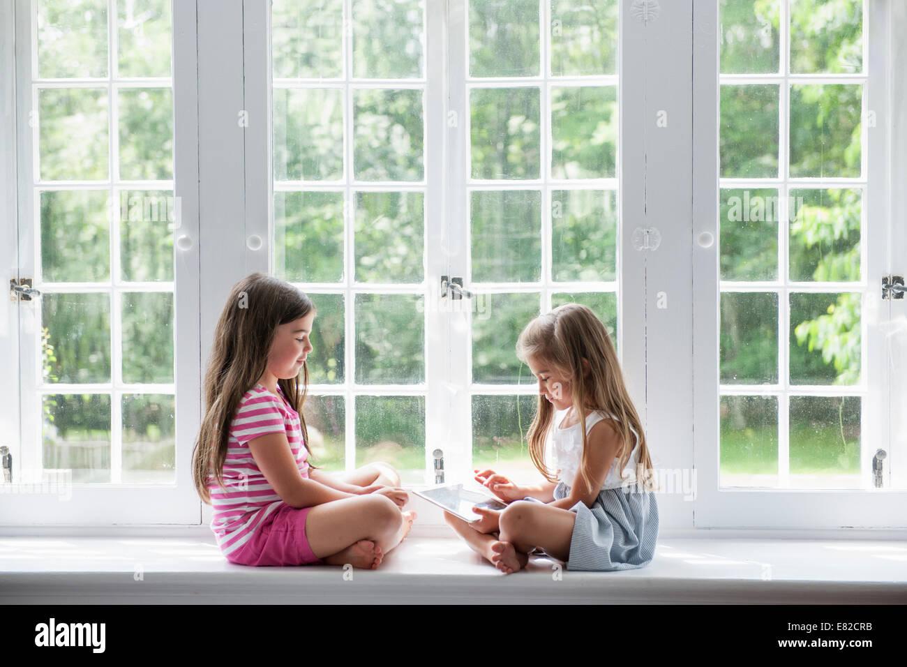 Deux jeunes filles, jouant, le partage d'une tablette numérique. Photo Stock