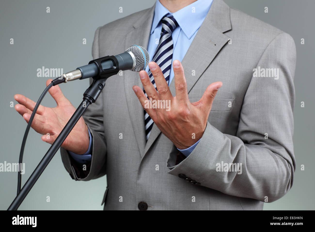 Discours avec microphone et geste de la main Photo Stock