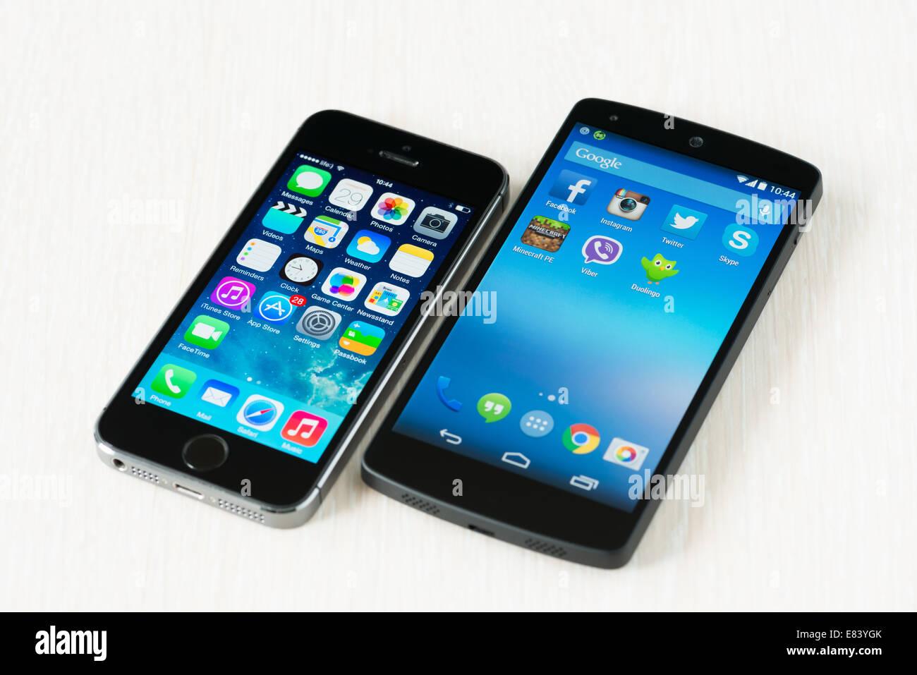 Close-up shot of brand new Apple iPhone 5S et les smartphones Google Nexus 5 couché sur un bureau. Banque D'Images