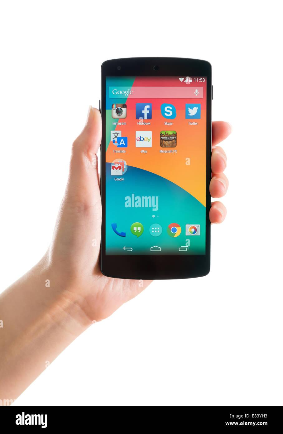 Studio shot of woman holding tout nouveau Google Nexus 5, propulsé par Android 4.4, version fabriqué par LG Electronics. Banque D'Images