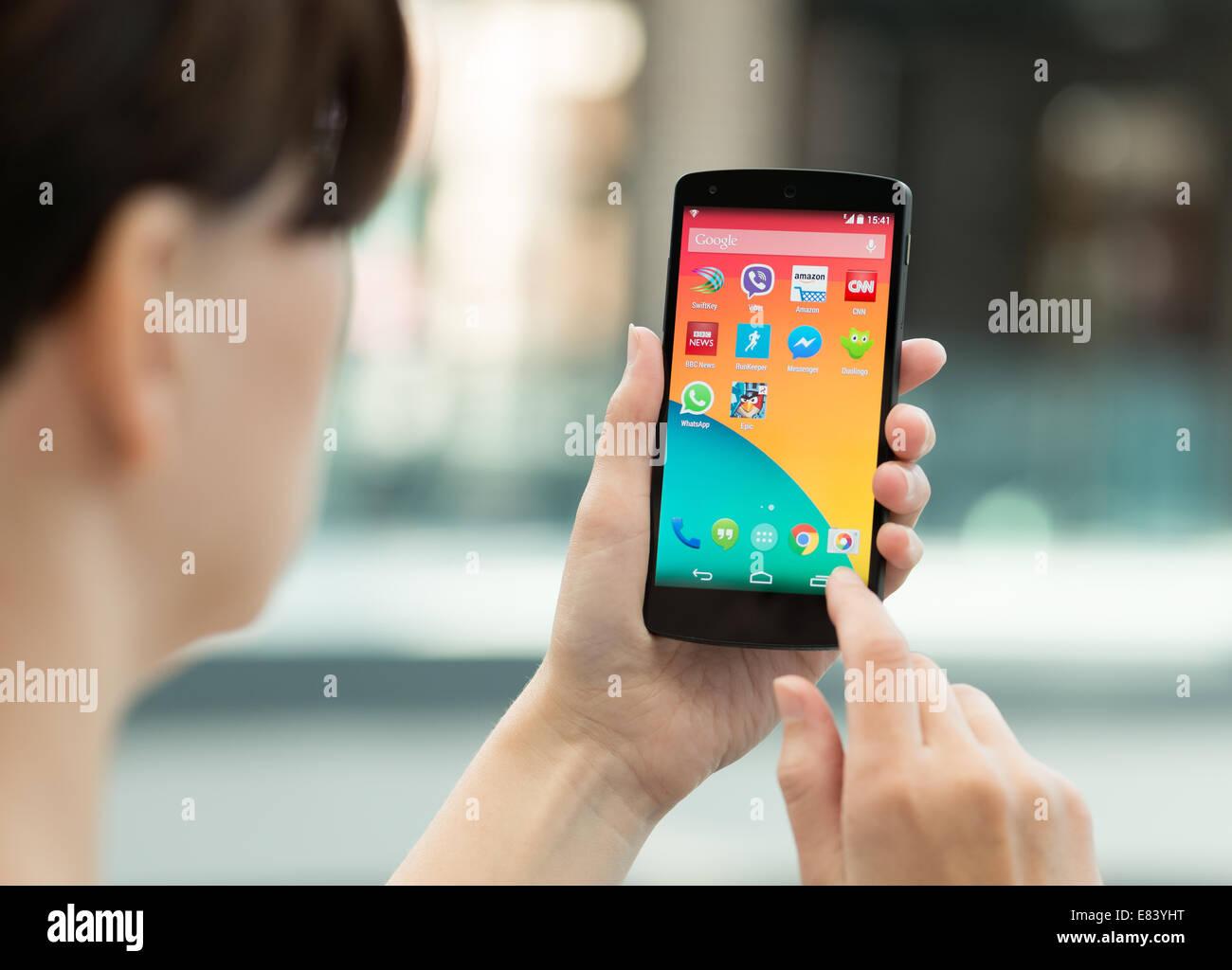 Femme à l'aide d'un tout nouveau Google Nexus 5 en plein air Banque D'Images