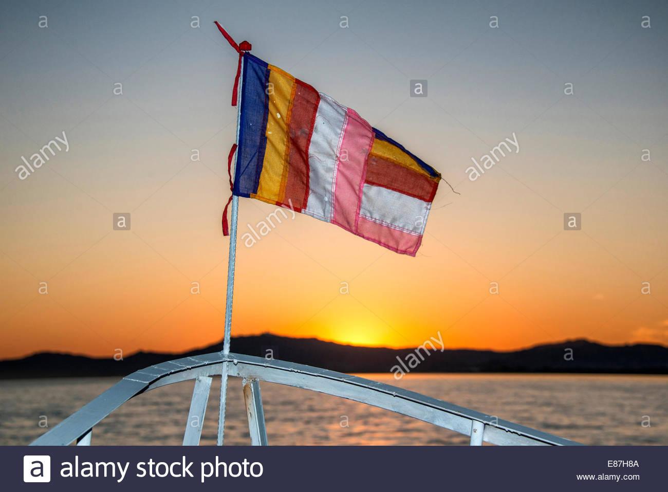 Drapeau du Myanmar sur un bateau sur le fleuve Irrawaddy au coucher du soleil Banque D'Images