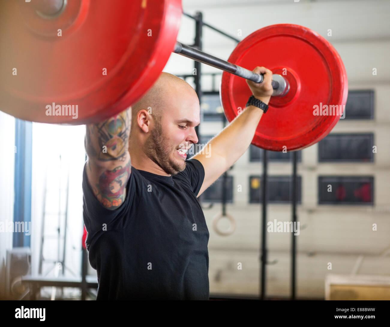 L'exercice avec l'athlète à gym haltères Photo Stock