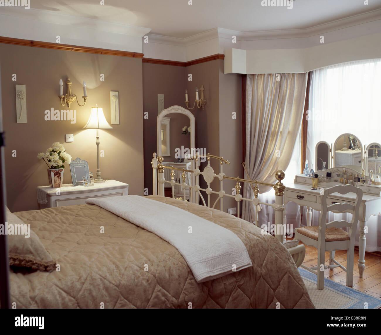Jeter la crème et beige foncé quilt sur laiton lit dans chambre ...
