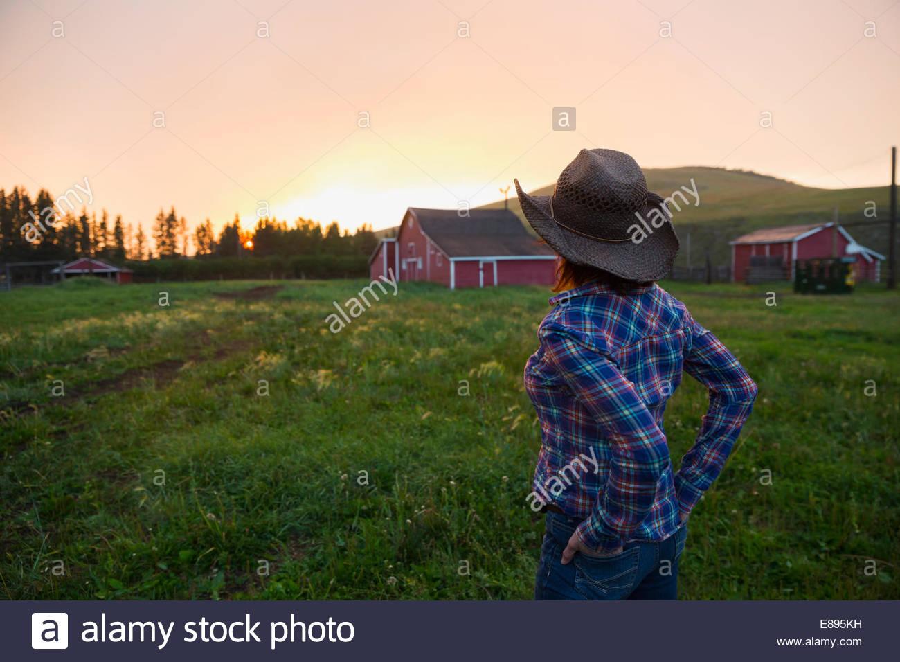 Femme au chapeau de cowboy en regardant le coucher de soleil sur barn Photo Stock