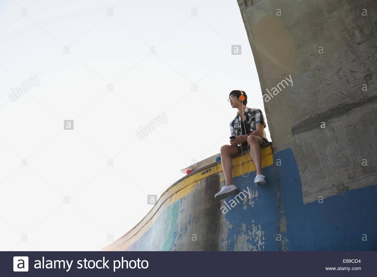 Teenage boy sur la rampe d'accès au parc de planche à roulettes Photo Stock