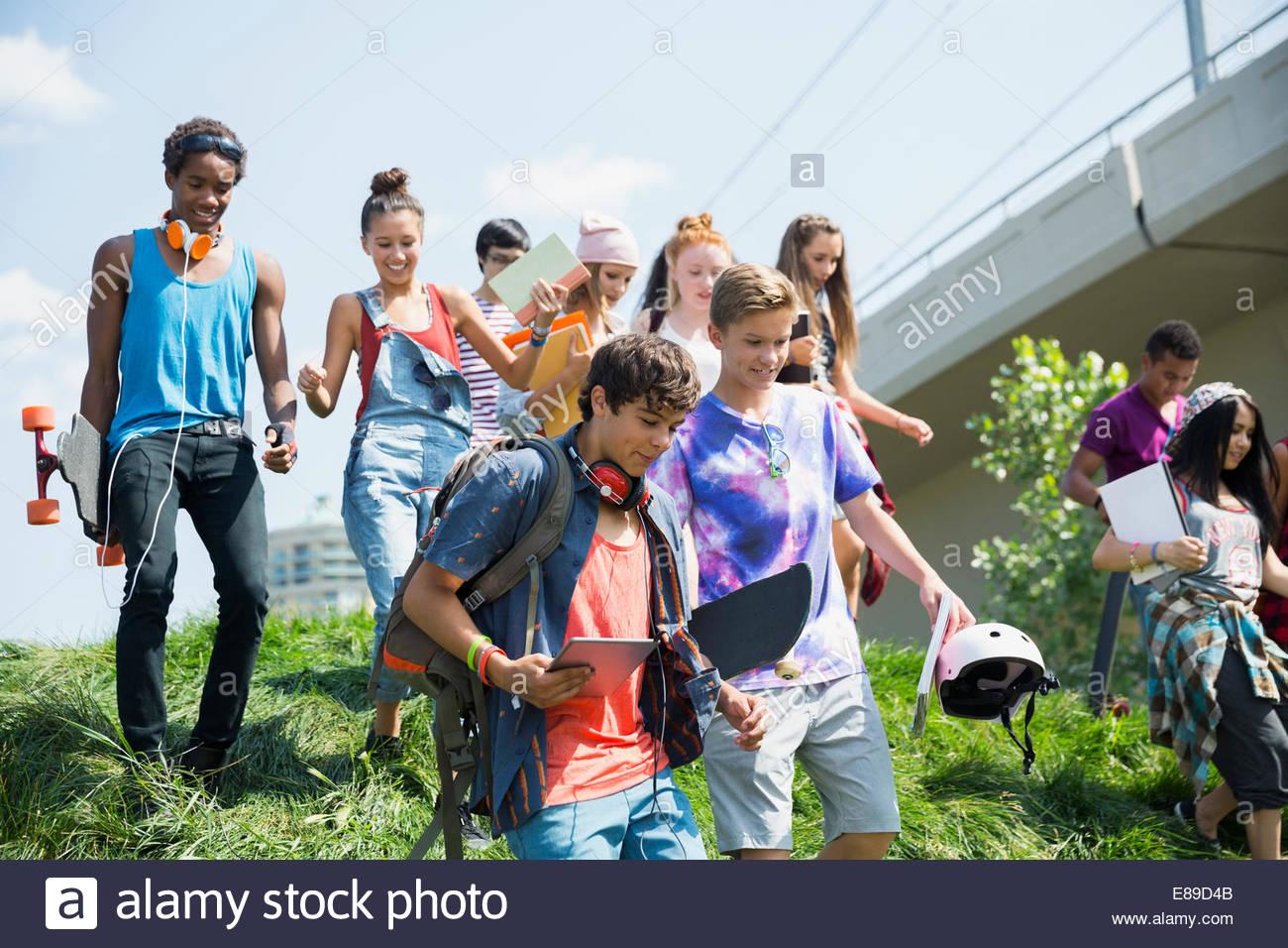 Les adolescents en descendant la pente gazonnée Photo Stock