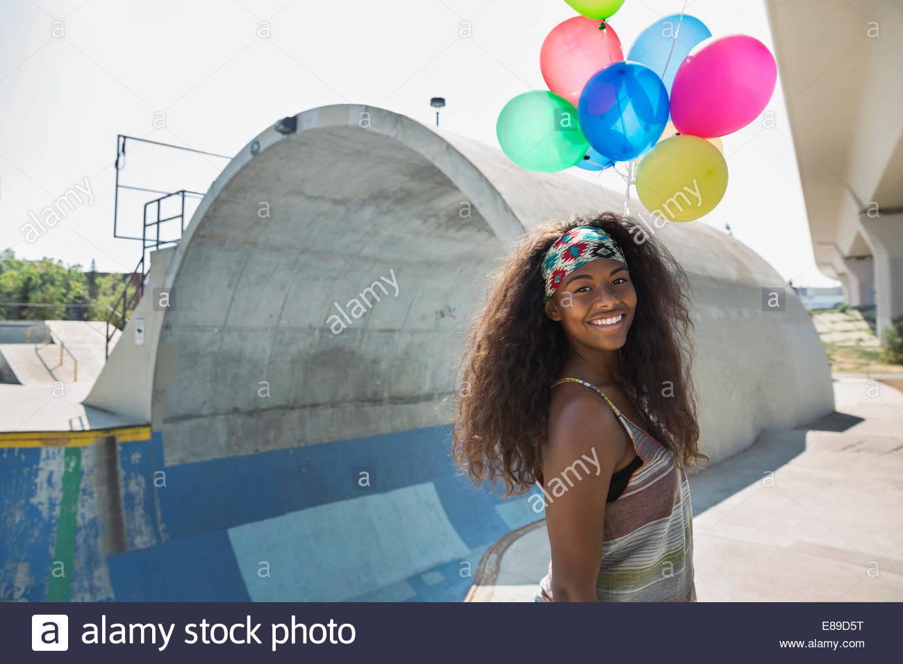 Teenage girl with balloons at parc de planche à roulettes Photo Stock