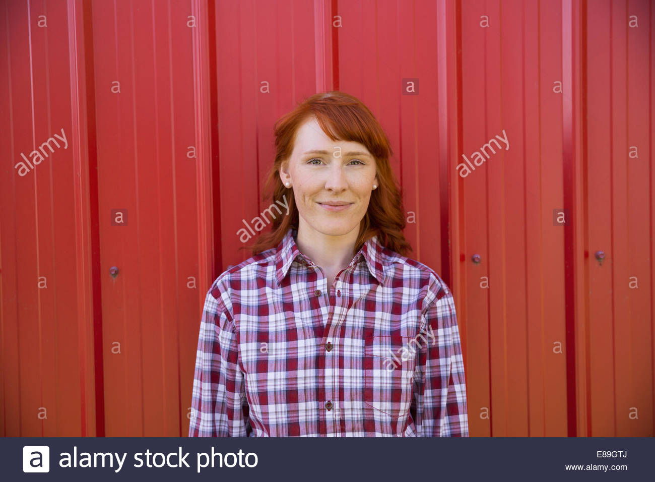 Portrait of smiling woman against red wall Photo Stock