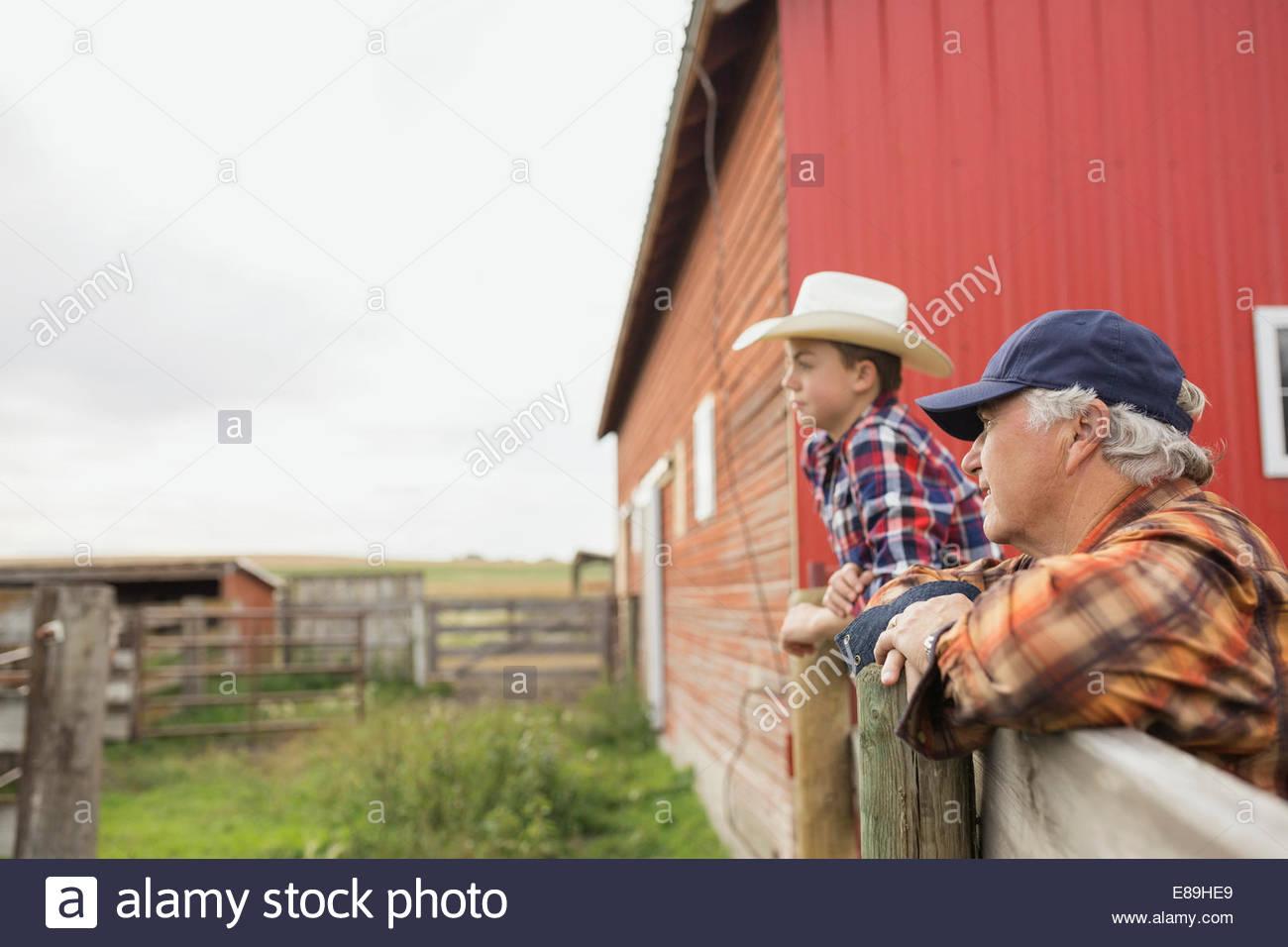 Grand-père et petit-fils leaning on fence on farm Photo Stock