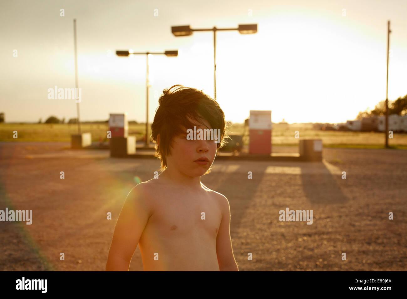 Shirtless boy at gas station Photo Stock