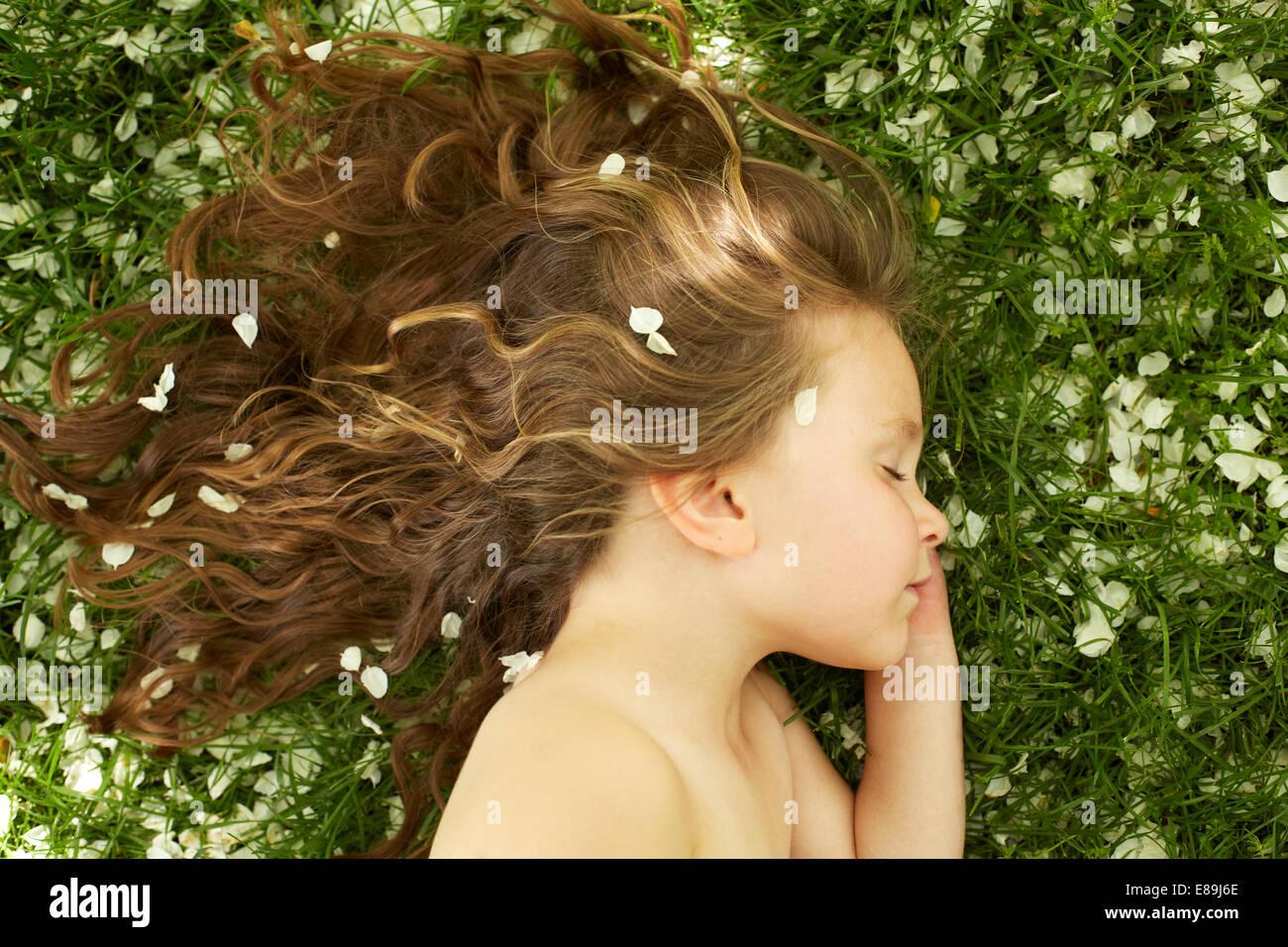 Girl sleeping in champ avec pétales de fleurs Photo Stock