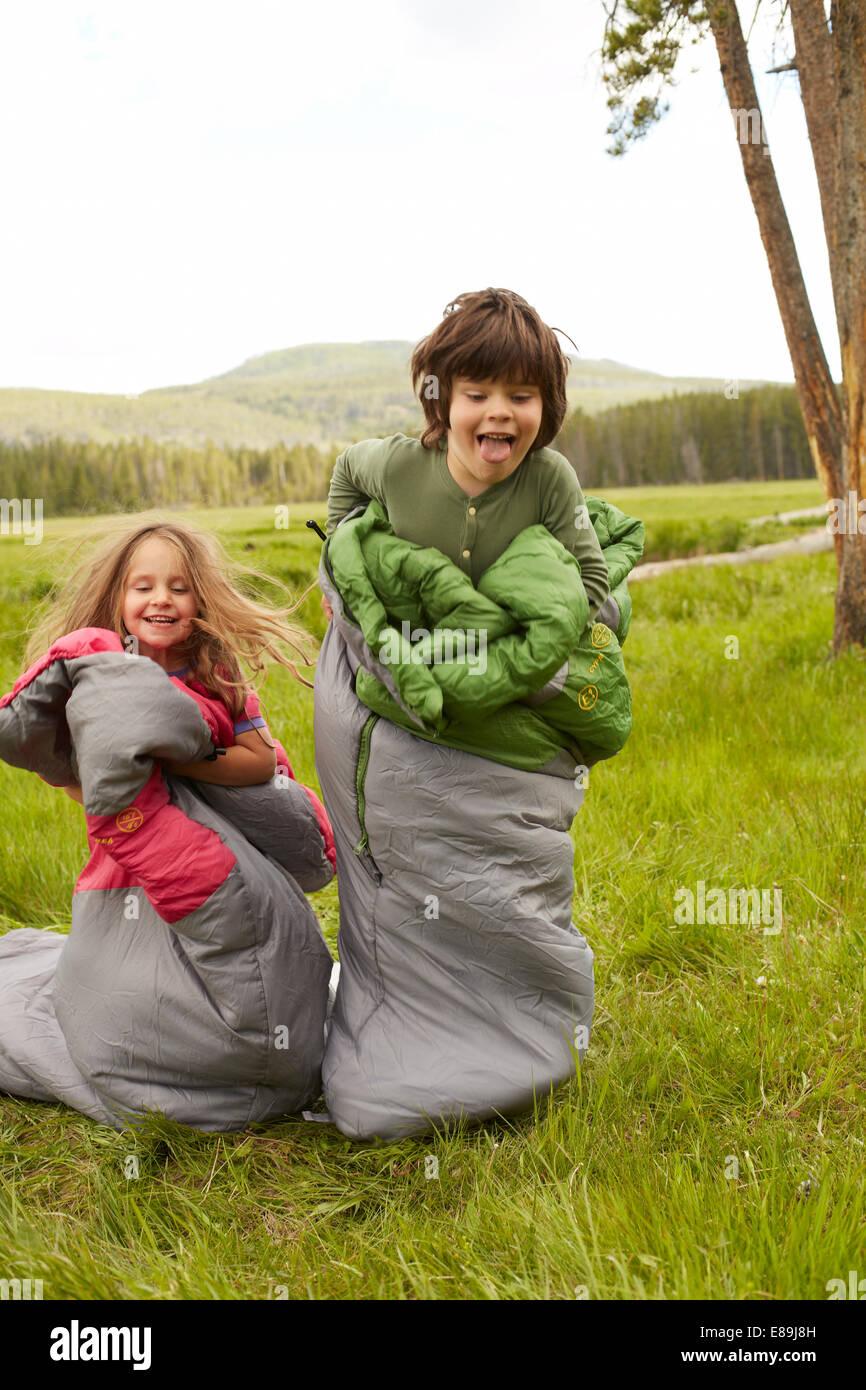 Garçon et fille sac course dans des sacs de couchage Photo Stock