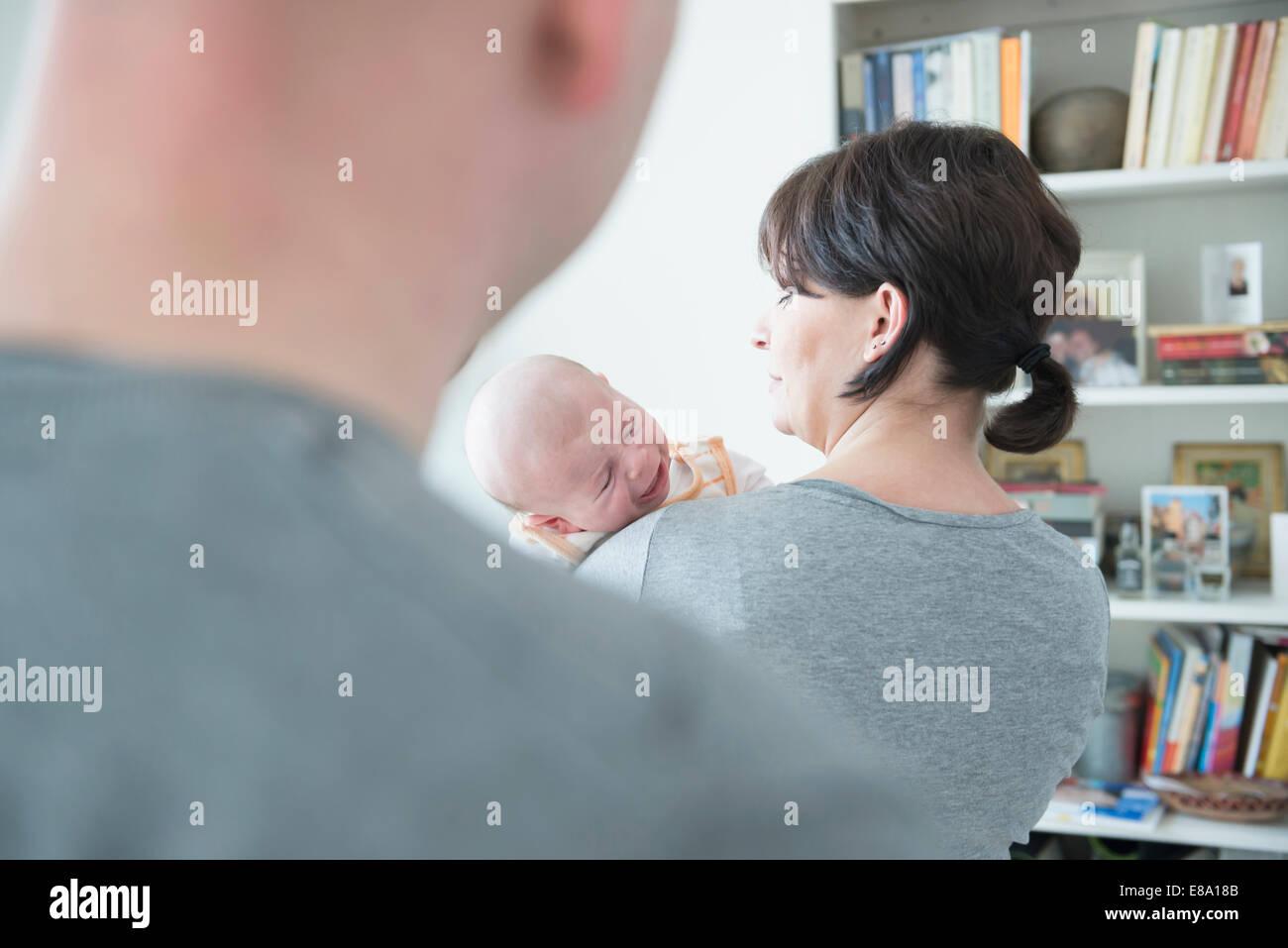 La mère pleurant son fils pleurer tandis que père en premier plan Photo Stock