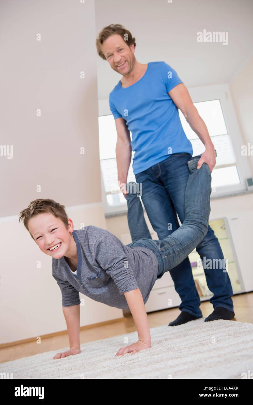 Le père et le fils ayant une course de brouettes à la maison Banque D'Images