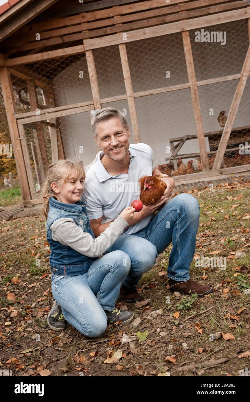 Père et fille avec du poulet à la ferme biologique Photo Stock