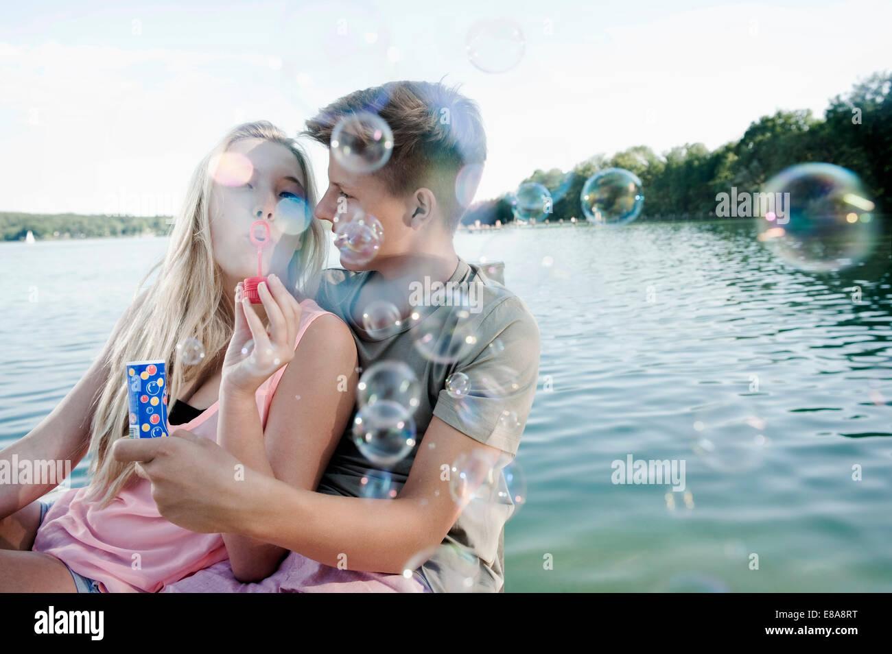 Couple soufflant des bulles de savon sur une jetée au lac Photo Stock