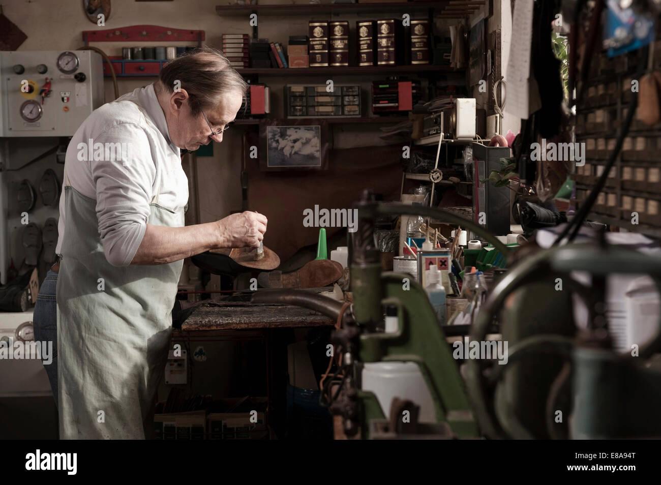 Cordonnier travaillant en atelier Photo Stock
