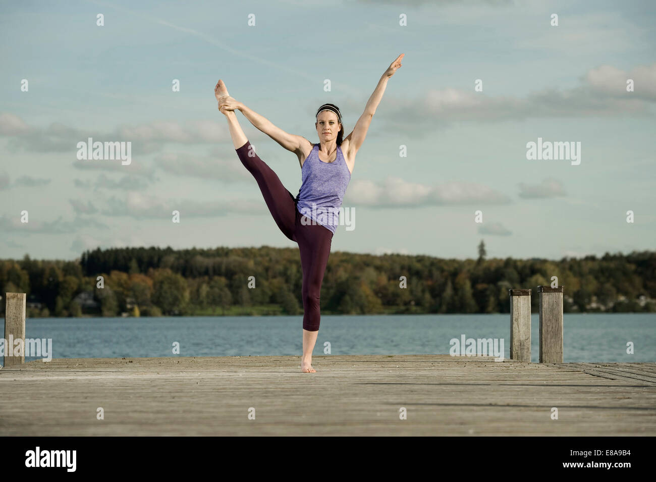 Woman practicing yoga on Jetty, Woerthsee, Bavière, Allemagne Photo Stock