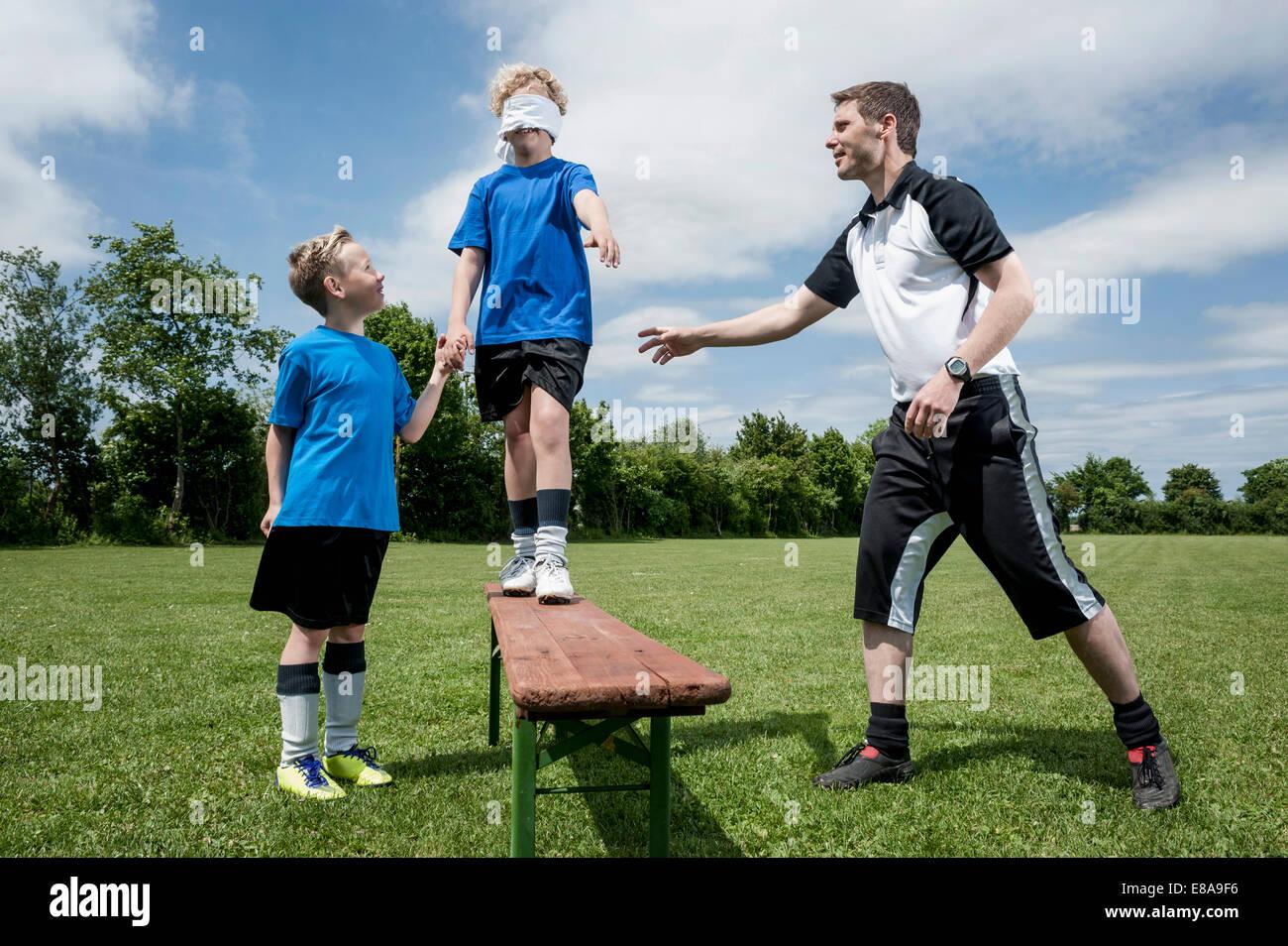 Entraîneur de football l'enseignement aux jeunes confiance joueur Photo Stock