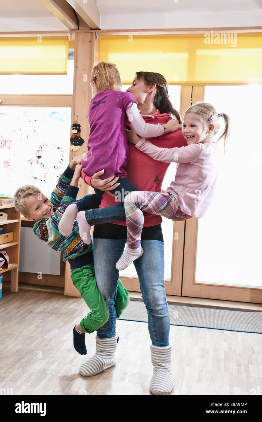 Éducateur femelle rampaging avec trois enfants en maternelle Photo Stock