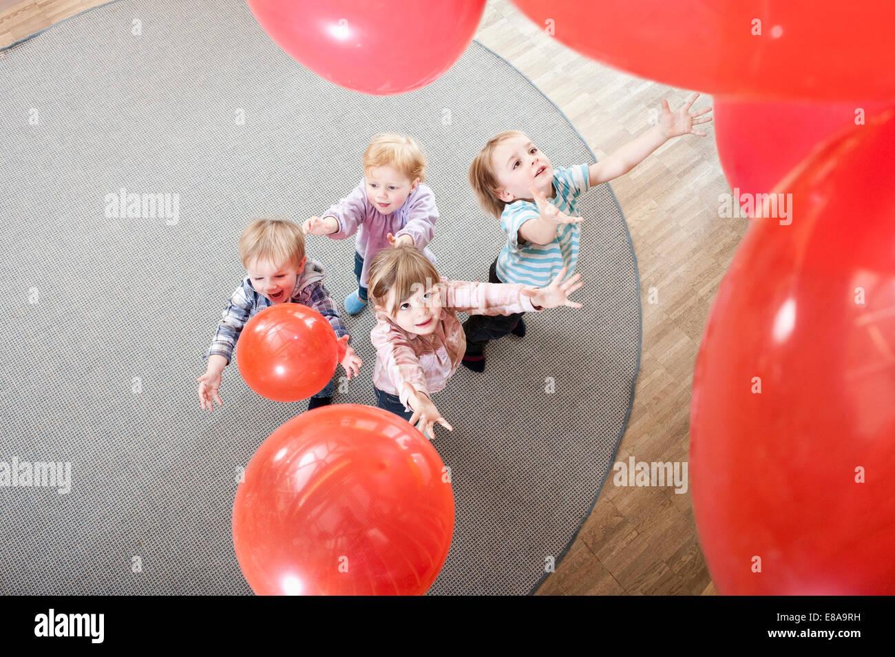Quatre enfants qui jouent avec des ballons rouges en maternelle, elevated view Photo Stock