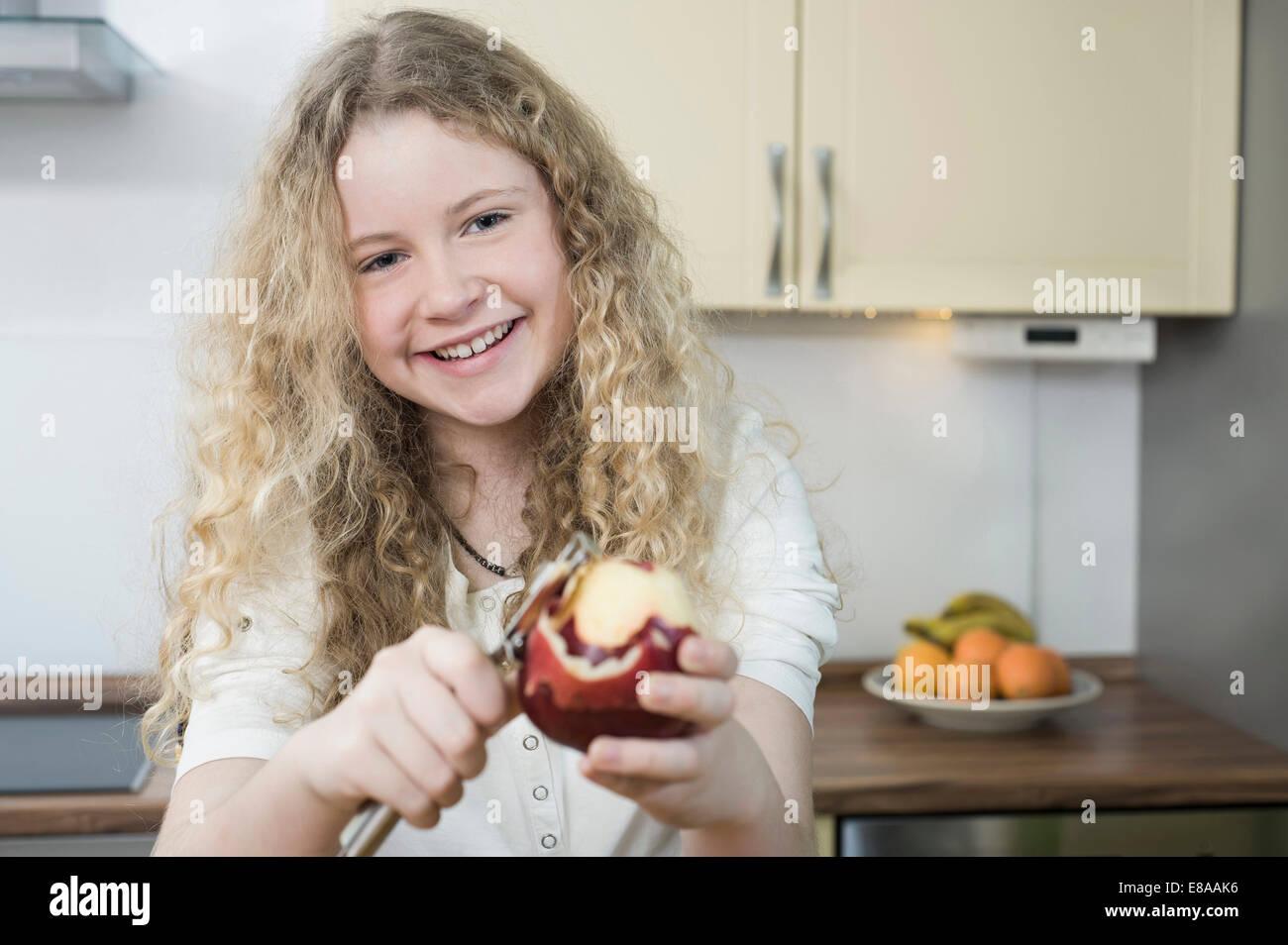 Fille en cuisine peeling apple Photo Stock