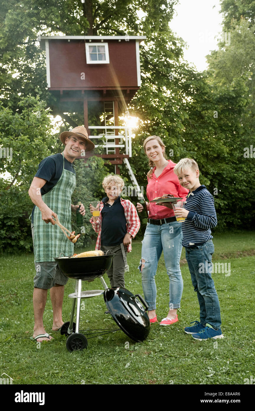 Jeune famille jardin barbecue kids tree-house Photo Stock