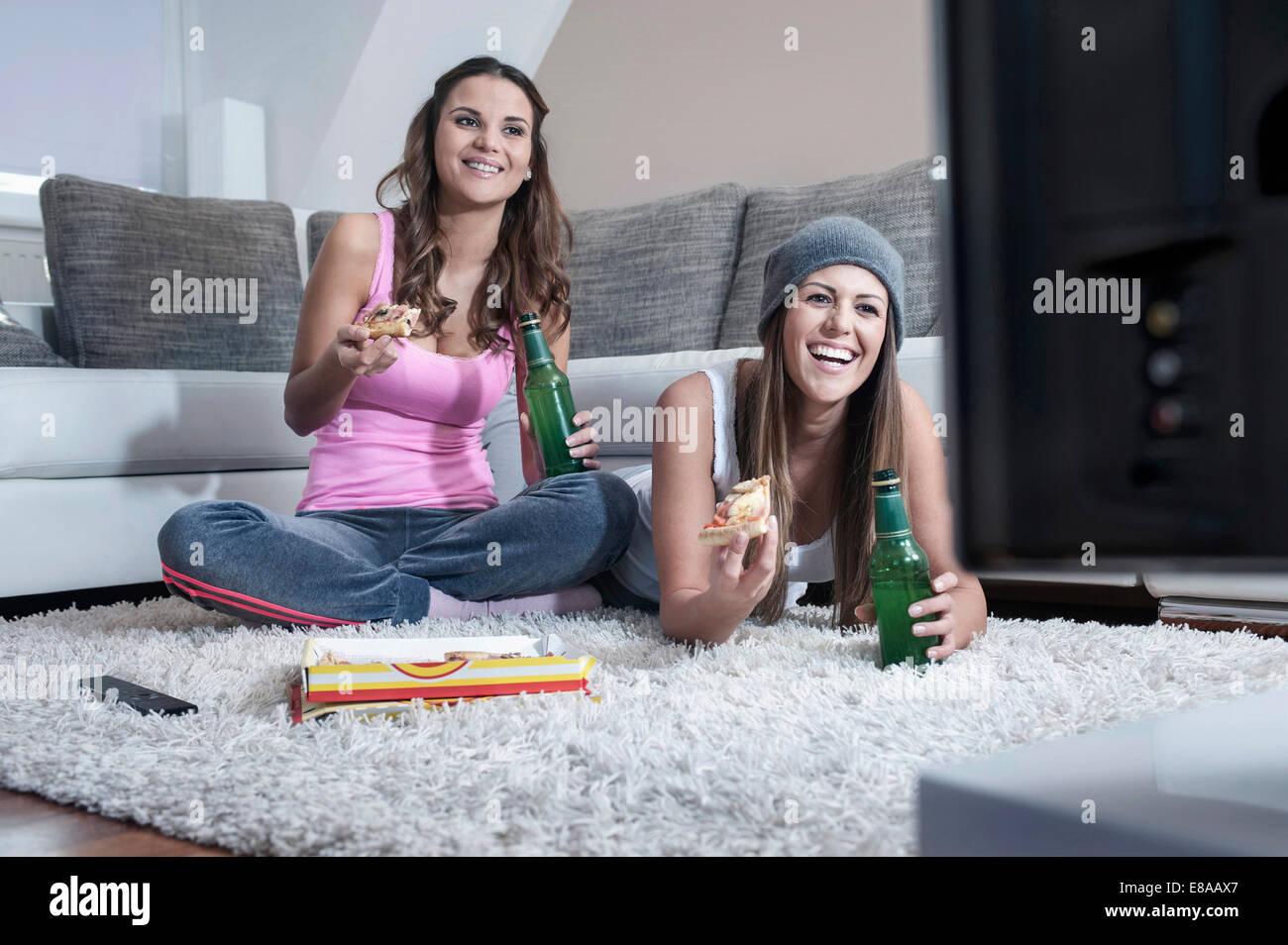 Deux amies côte à côte sur un tapis à la maison à regarder la télévision Photo Stock