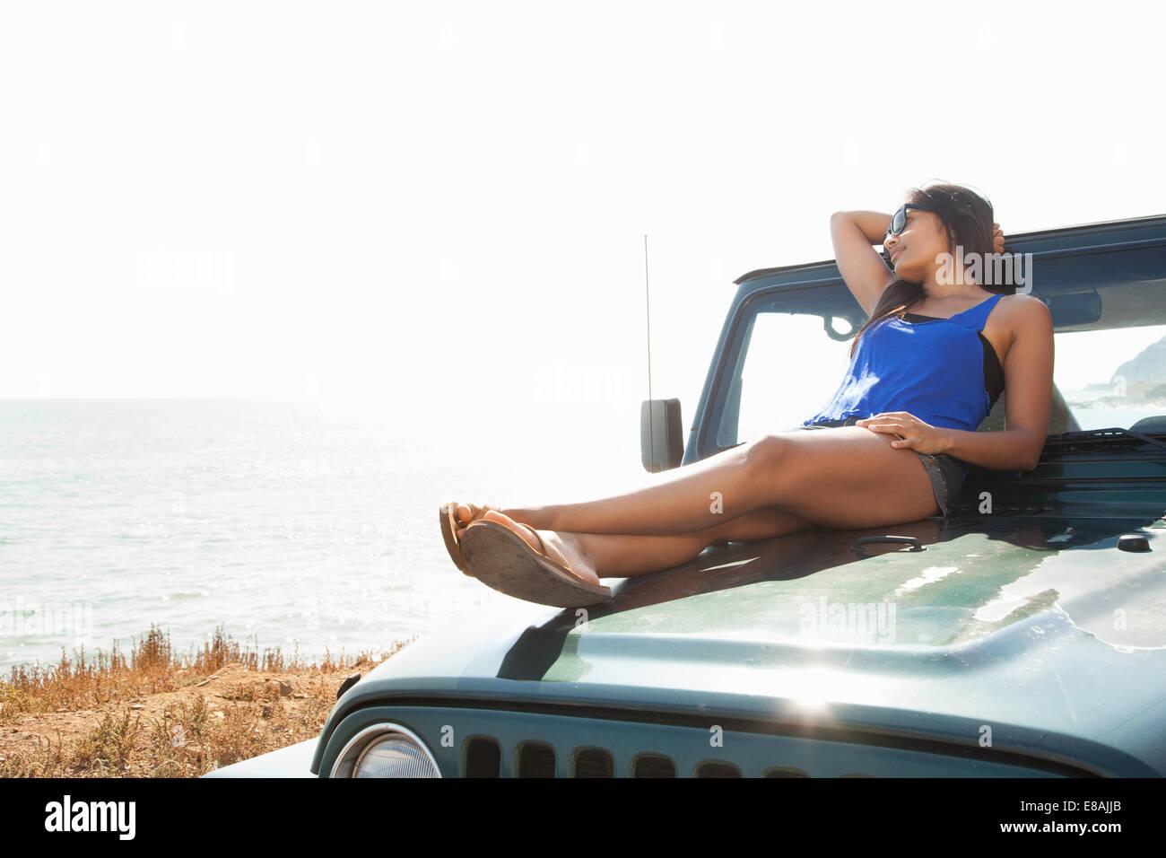 Jeune femme couchée sur le capot de la jeep à côte, Malibu, California, USA Photo Stock