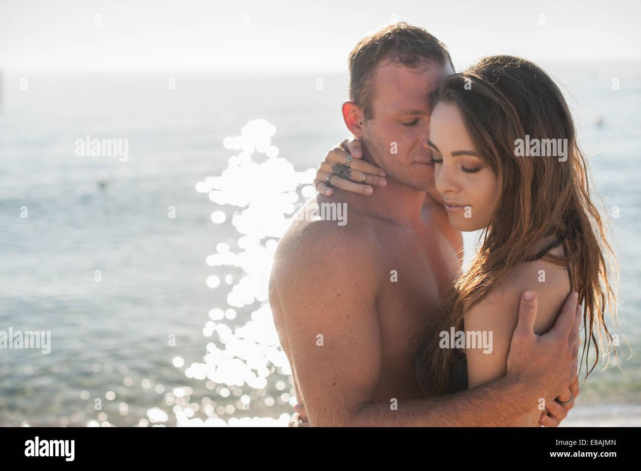 Young couple embracing on beach, Castiadas, Sardaigne, Italie Photo Stock