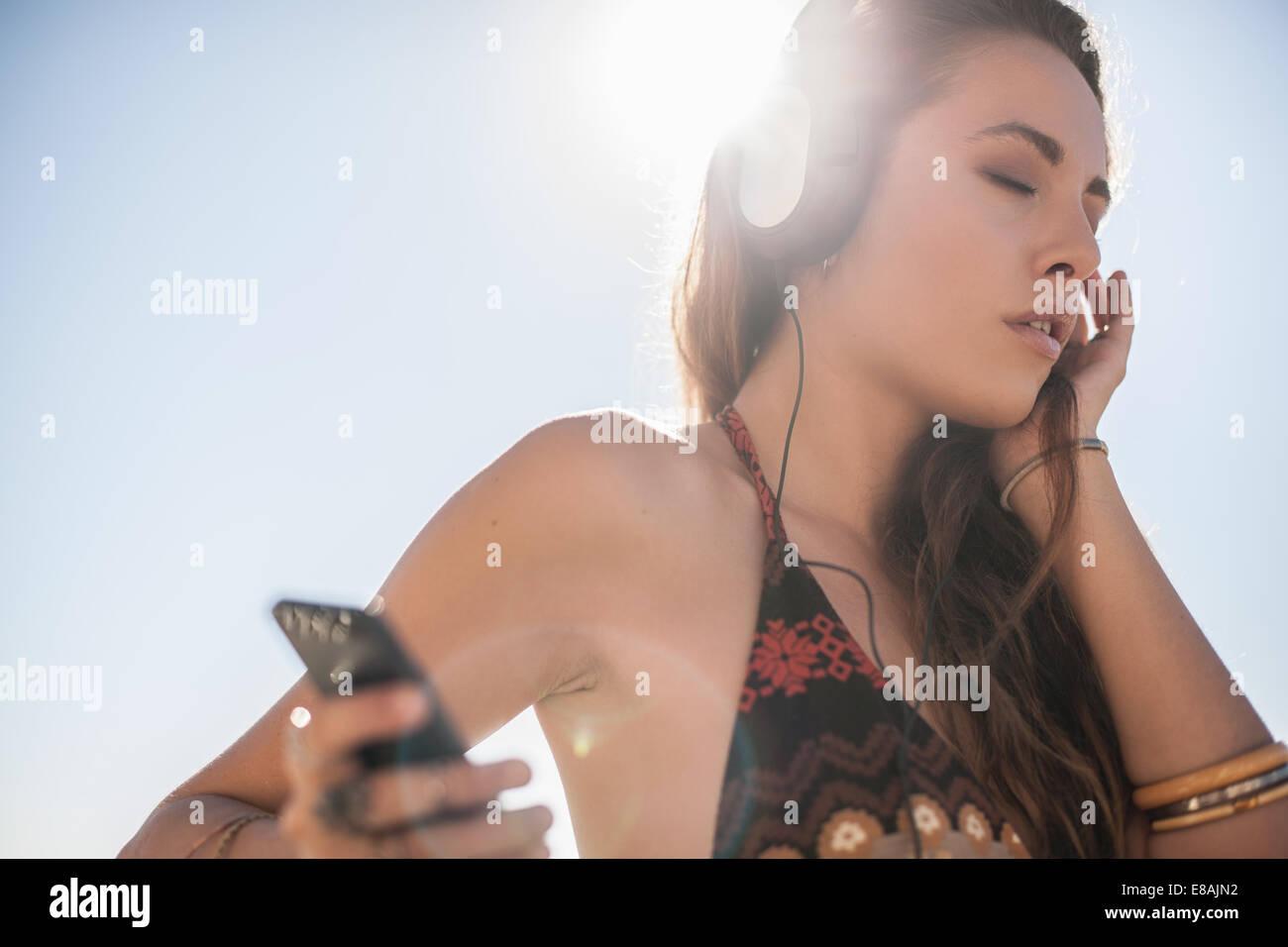 Jeune femme avec les yeux fermés listening to music on headphones at beach, Castiadas, Sardaigne, Italie Photo Stock