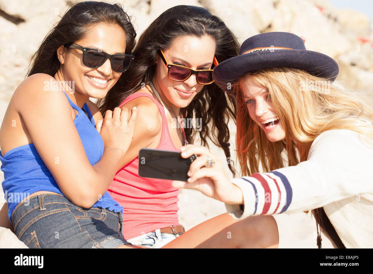 Trois jeunes femmes prenant des selfies smartphone on beach, Malibu, California, USA Photo Stock