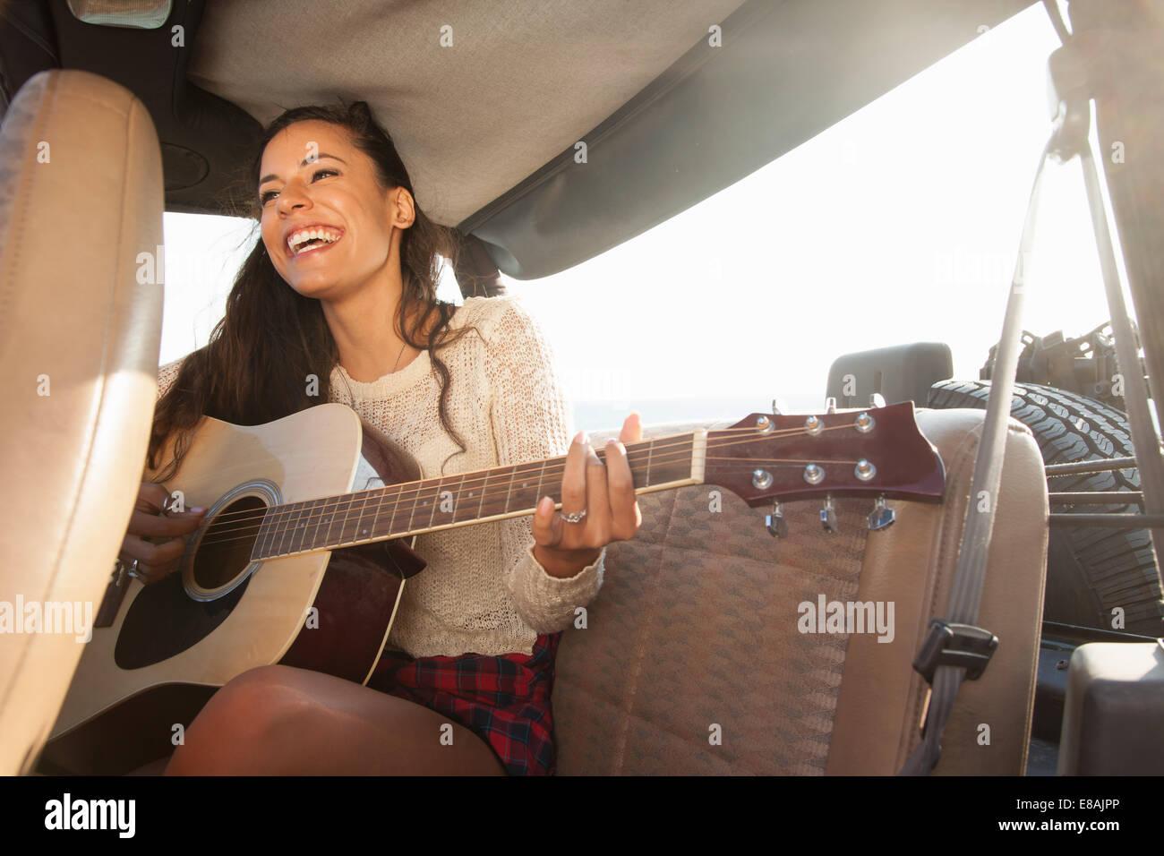 Jeune femme jouant de la guitare acoustique à l'arrière de jeep Photo Stock