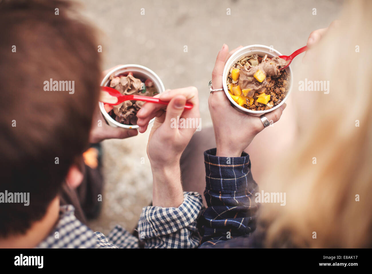 Couple eating de pots de yaourt glacé traiter Photo Stock