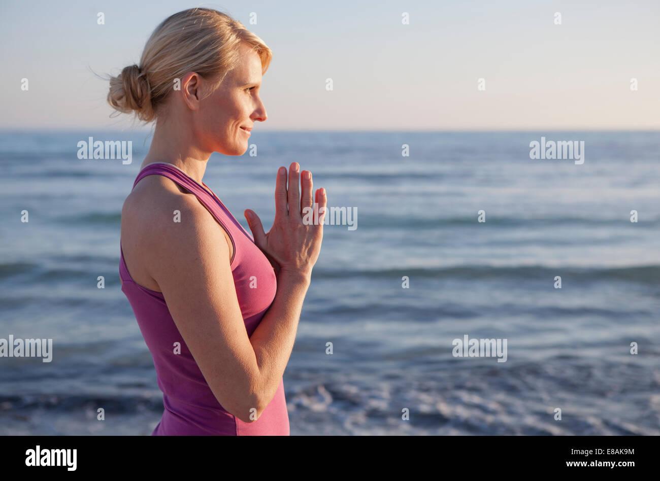 Woman in yoga pose de prière sur la plage Photo Stock