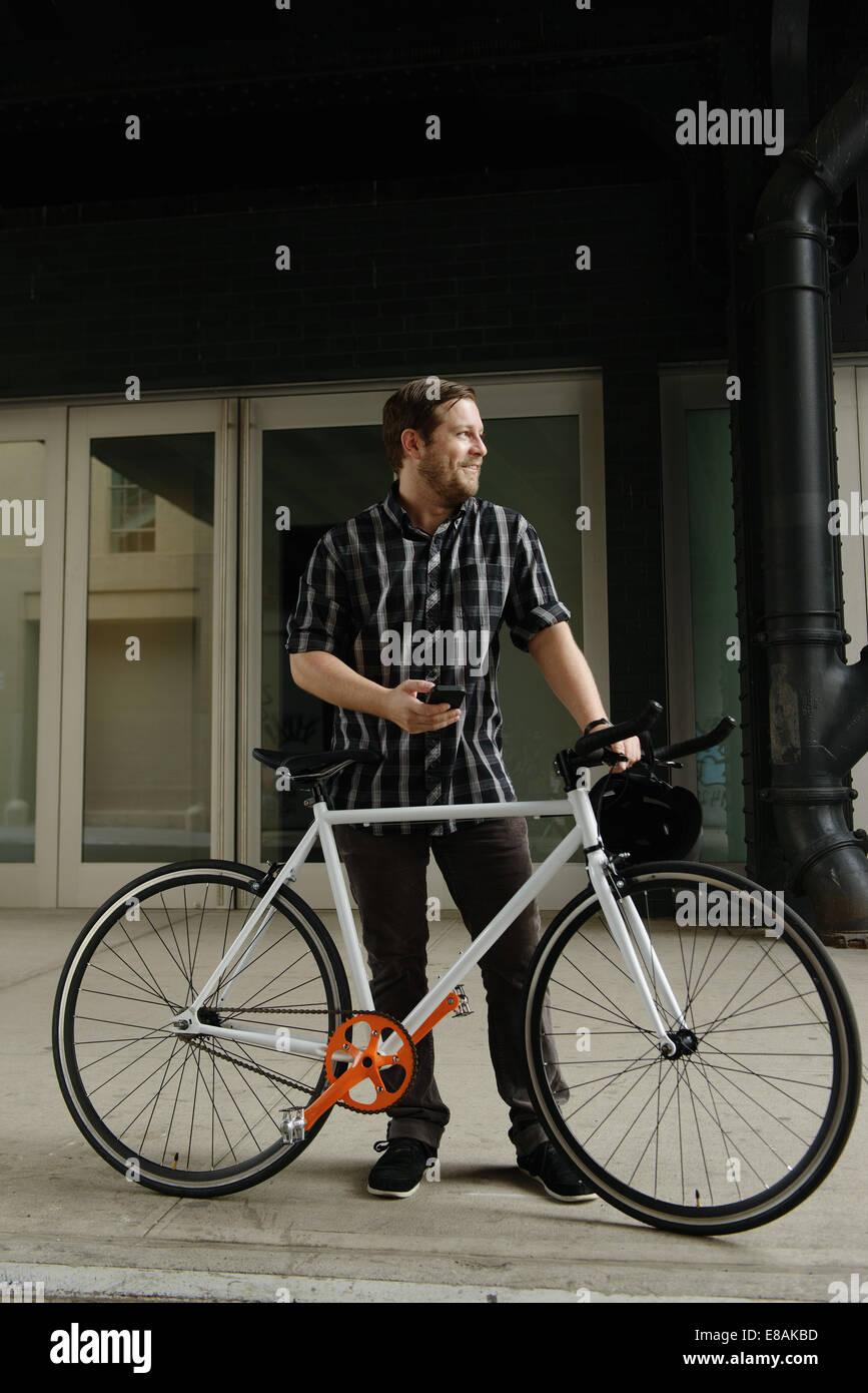 Cycle masculin messenger sens sur smartphone à l'extérieur du bureau Photo Stock