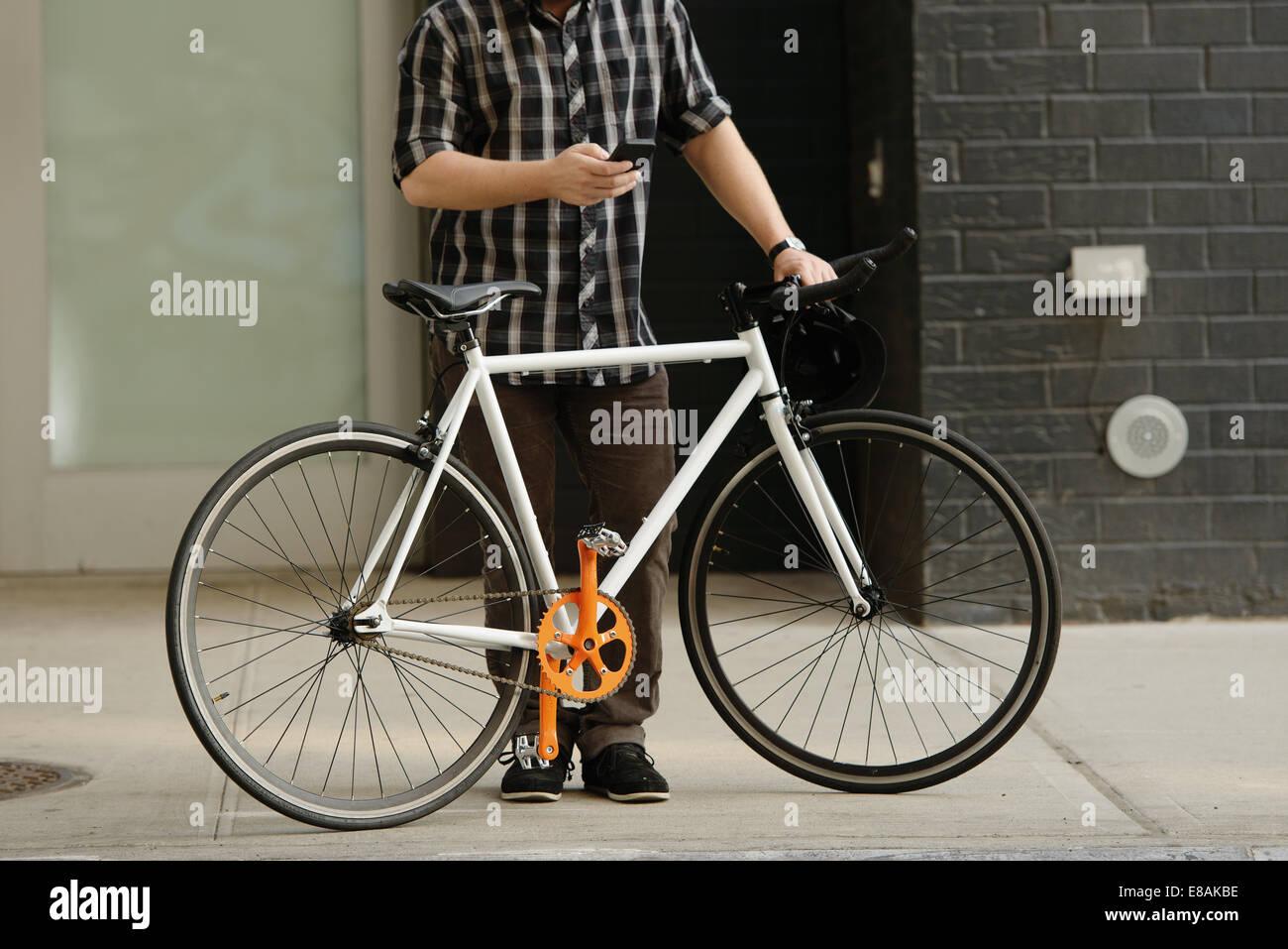 Vue vers le bas du cou de l'homme au sens du cycle messenger sur smartphone à l'extérieur du bureau Photo Stock