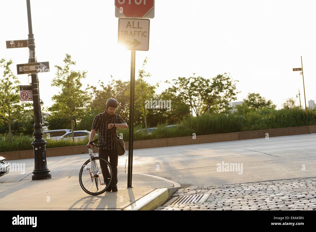 Cycle masculin messenger contrôle de temps sur route Photo Stock