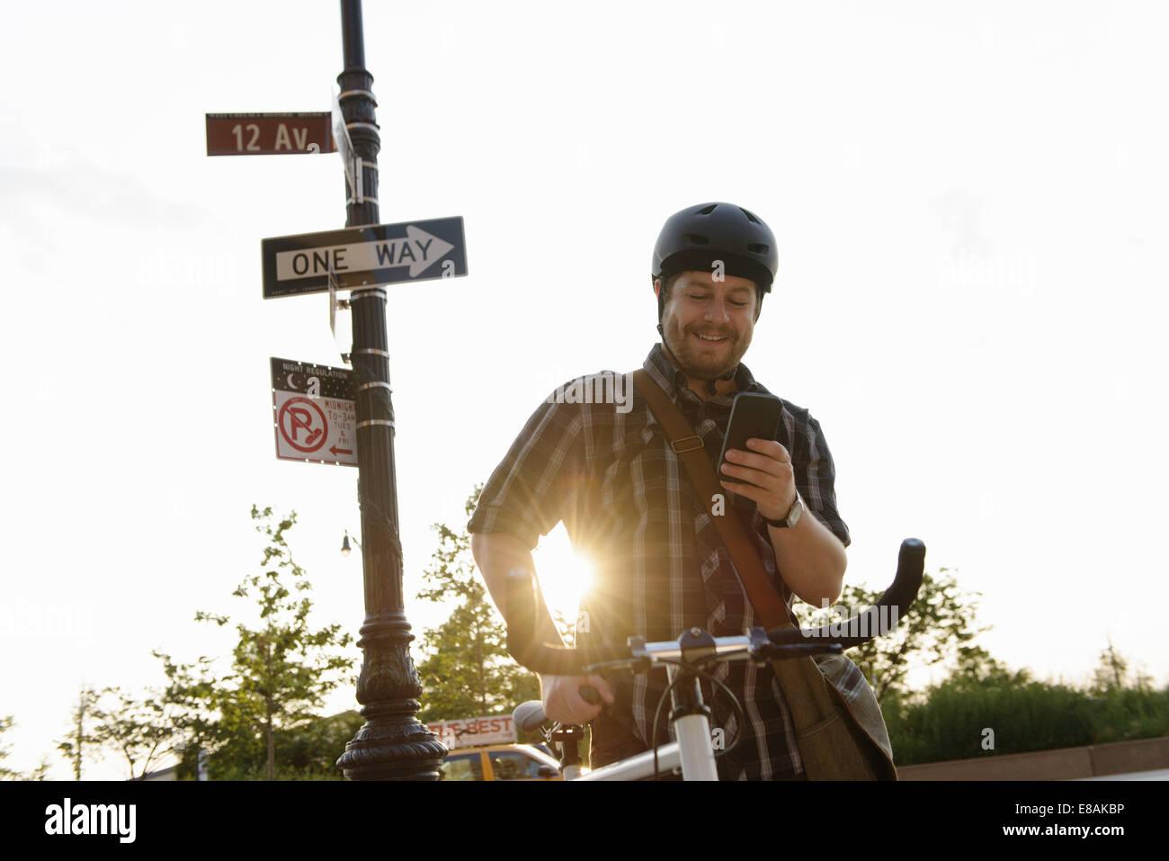 Cycle masculin messenger contrôle des messages texte sur smartphone Photo Stock